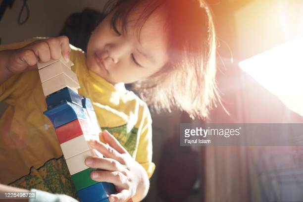 asian child playing with bricks - joy stock pictures, royalty-free photos & images