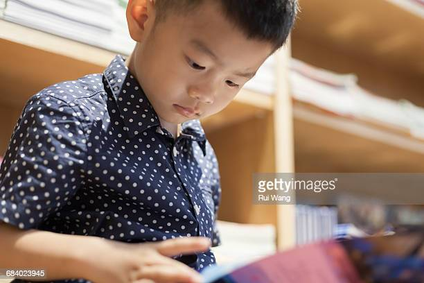 Asian child reading book indoors