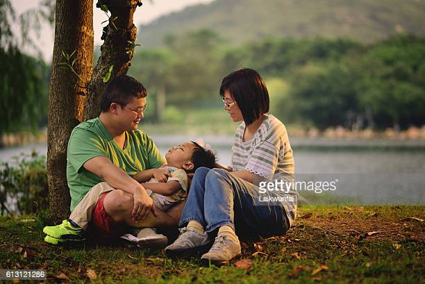 Asian child sleeping in arms of parents