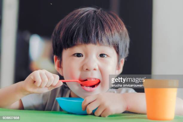 asian children eating scooping the food on the table. - very young thai girls stock photos and pictures