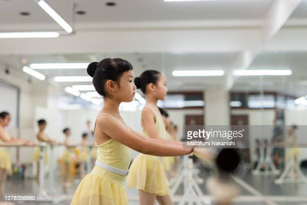asian children of a ballet students taking a lesson with ballet lesson bar. - japan stock pictures, royalty-free photos & images