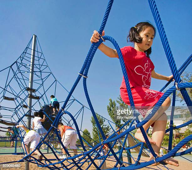 Asian children outside climbing on a park play structure.