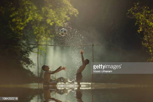 asian children playing football at the river. - kids pool games stock pictures, royalty-free photos & images
