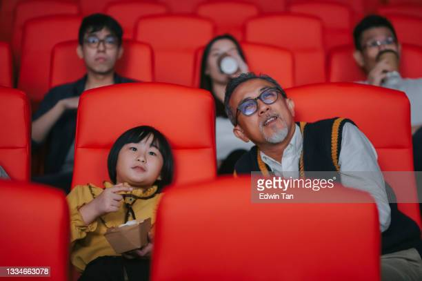asian chinese active senior man and his granddaughter enjoy watching movie in cinema movie theatre - film premiere stock pictures, royalty-free photos & images