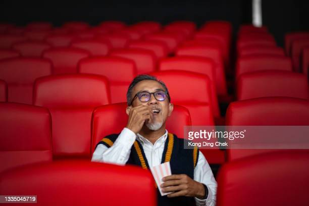asian chinese active senior man enjoying his snack while watching movie in movie theater cinema alone - film premiere stock pictures, royalty-free photos & images