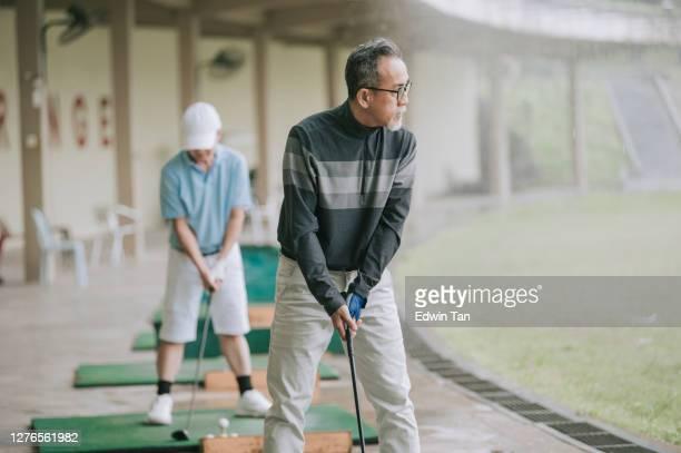 アジアの中国のアクティブなシニア男性ゴルファーは、ゴルフのドライビングレンジで彼のダイバーゴルフクラブをティーオフし、スイング - ゴルフ練習場 ストックフォトと画像