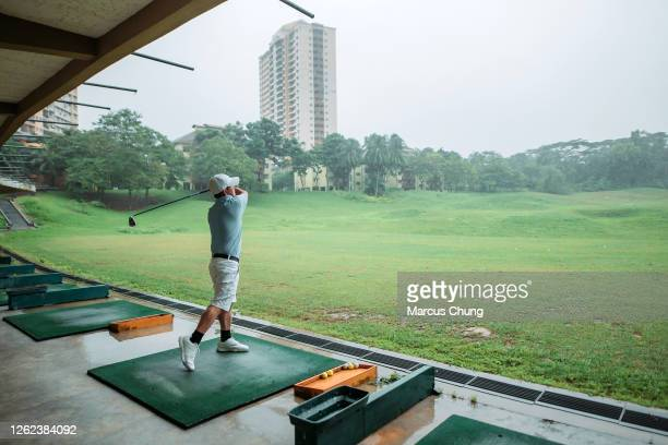 asian chinese active senior man golfer teeing off and swing his golf club at golf driving range - driving range stock pictures, royalty-free photos & images