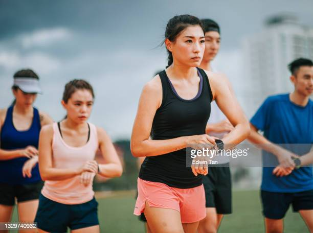 asian chinese athletes lining up getting ready start timing using fitness tracer smart watch time before running at track and run towards finishing line in the morning at track and field stadium - forward athlete stock pictures, royalty-free photos & images
