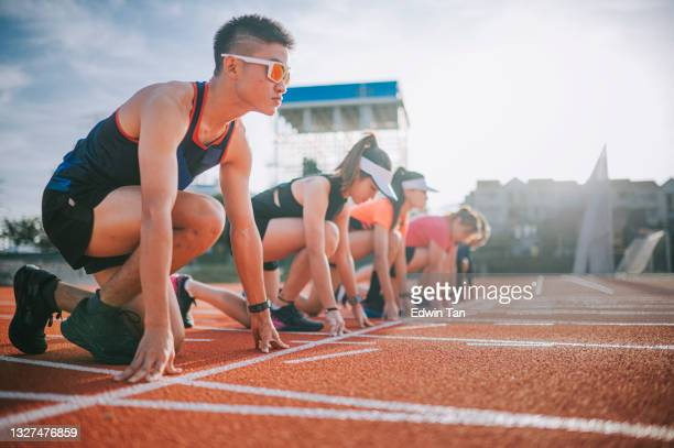 asian chinese athletes lining up getting ready starting line running at track and run towards finishing line in the morning at track and field stadium - forward athlete stock pictures, royalty-free photos & images