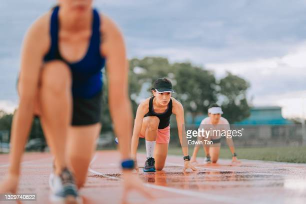asian chinese athletes lining up  starting line aerodynamic shape getting ready to run at track rainy late evening in stadium - forward athlete stock pictures, royalty-free photos & images