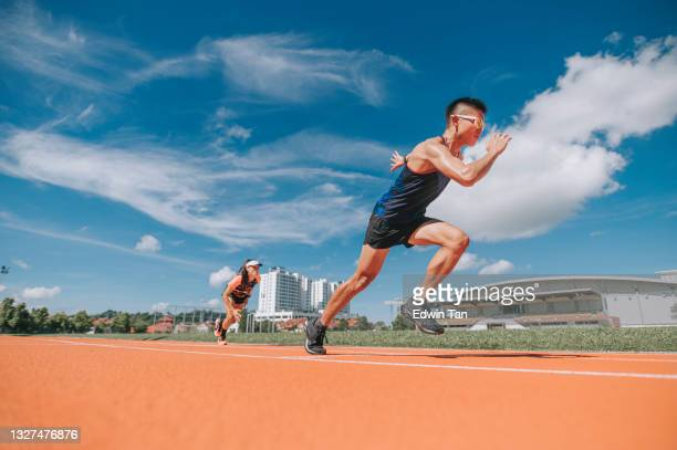 asian chinese athletes sprint running at track and run towards finishing line in the morning at track and field stadium - forward athlete stock pictures, royalty-free photos & images