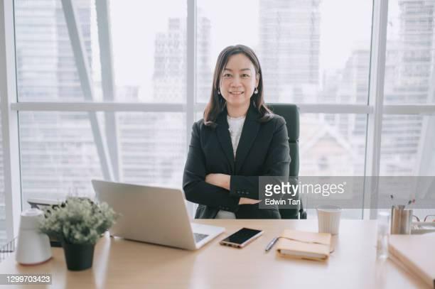 アジアの中国の美しい女性ceoは、オフィスで彼女の机に微笑むカメラを見て - エグゼクティブディレクター ストックフォトと画像