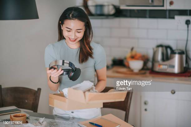 asian chinese beautiful woman receiving unpacking trying on her headphone from online shopping at kitchen - unboxing stock pictures, royalty-free photos & images