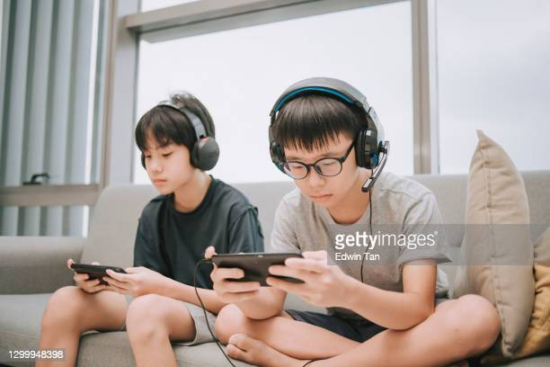 asian chinese brother playing multiplayer online gaming with headset in living room using smart phone connection - chinese ethnicity stock pictures, royalty-free photos & images