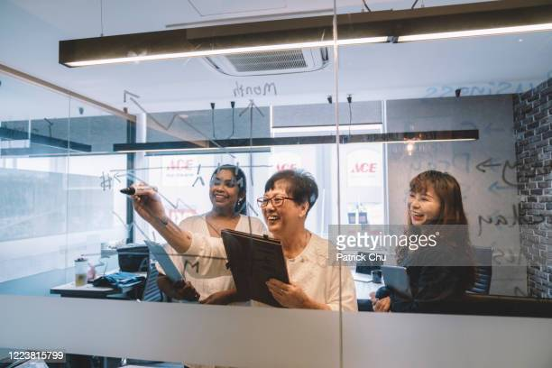 asian chinese businesswomen having brainstorming session with colleague at office - leanincollection stock pictures, royalty-free photos & images