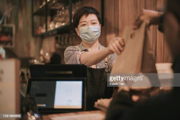 asian chinese cafe owner cashier passing food in recycled paper bag man to delivery person  picking up take away food - catering building stock pictures, royalty-free photos & images