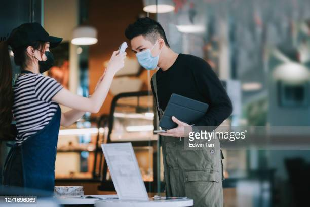 asian chinese cafe waitress checking body temperature for client as standard procedure and check in process before entering cafe as new normal - illness prevention stock pictures, royalty-free photos & images