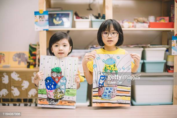 2 asian chinese children displaying their painting after the class at the art center looking at the camera - art product stock pictures, royalty-free photos & images
