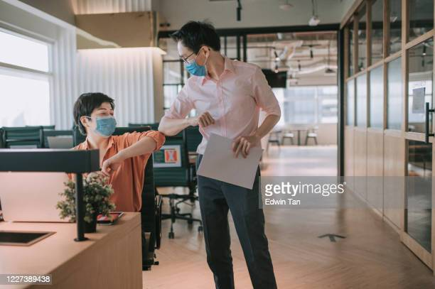 2 asian chinese colleague greeting on each other with new handshake style in office with protective mask on - new normal concept stock pictures, royalty-free photos & images