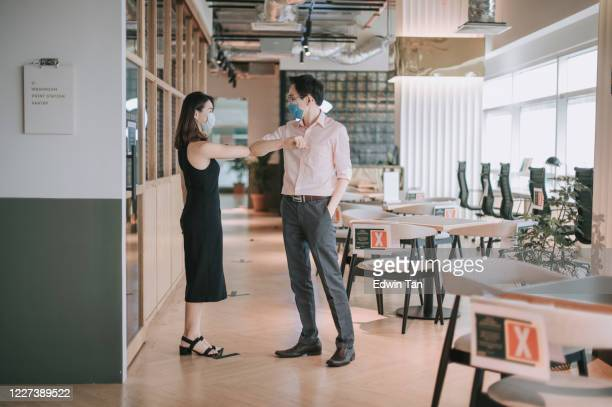 2 asian chinese colleague greeting on each other with new handshake style in office with protective mask on - new normal stock pictures, royalty-free photos & images