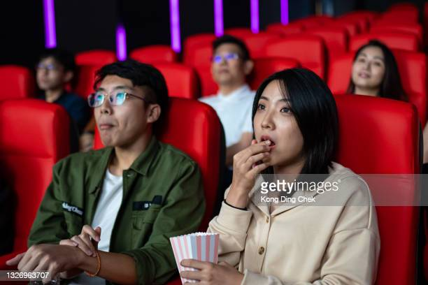 asian chinese couple at the movies eating popcorn and watching a film - film premiere stock pictures, royalty-free photos & images