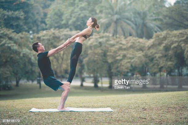 asian chinese couple performing yoga pose - acrobatic activity stock photos and pictures