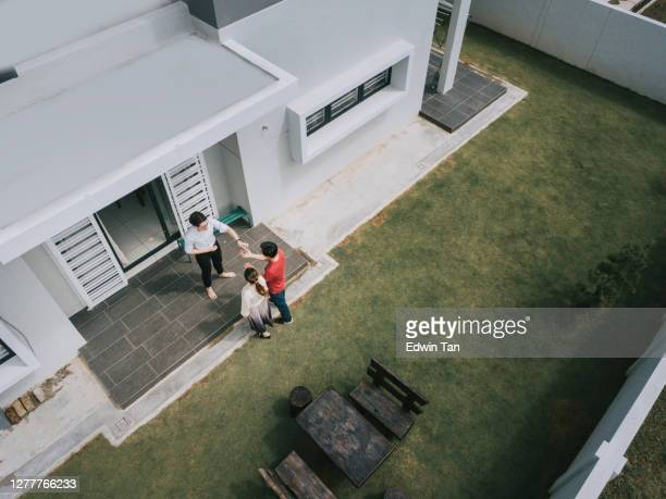 asian chinese couple receiving house keys from real estate agent outside new house - drone point of view stock pictures, royalty-free photos & images