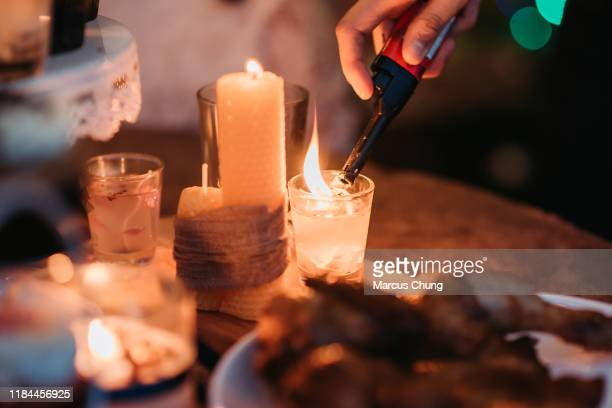 aziatische chinees het doen van de voorbereiding en licht op de kaars voor kerstfeest beginnen bij het dak van huis - kaars stockfoto's en -beelden