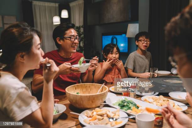 asian chinese family and cousins having reunion dinner at home - evening meal stock pictures, royalty-free photos & images