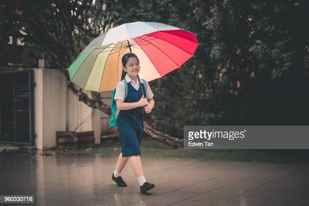 asian chinese family child coming back from school to home carrying multi-colored umbrella in rain