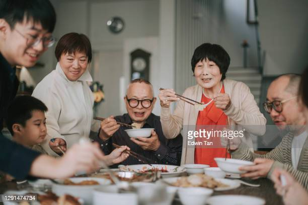 asian chinese family chinese new year reunion dinner having traditional dishes at dining table - asian and indian ethnicities stock pictures, royalty-free photos & images