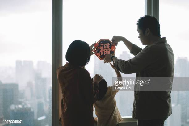 asian chinese family decorating their home during chinese new year celebration - wife stock pictures, royalty-free photos & images