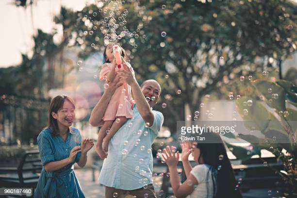 asian chinese family having fun bonding time in front of their house beside swimming pool - malay stock photos and pictures