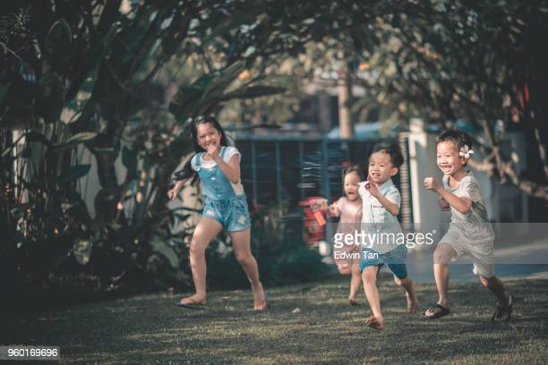 asian chinese family having fun bonding time in front of their house where children running towards parents
