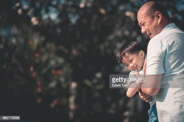 楽しい時を過す中国のアジアの家族の息子を運ぶ彼らの家の父の前で時間を結合 - マレーシア ストックフォトと画像