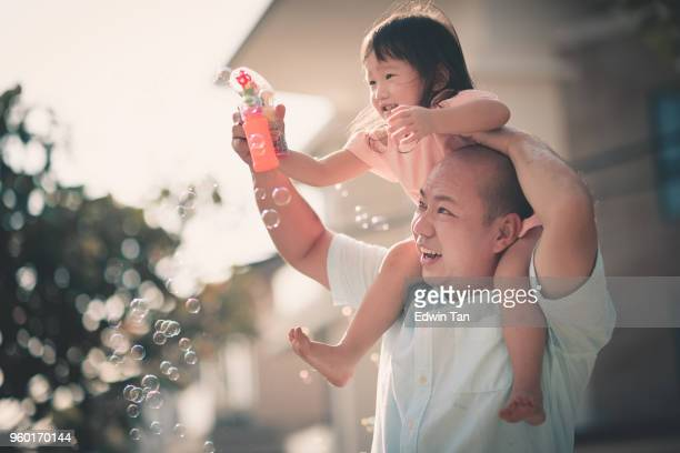 asian chinese family having fun bonding time in front of their house father having daughter over his shoulder - chinese family stock photos and pictures