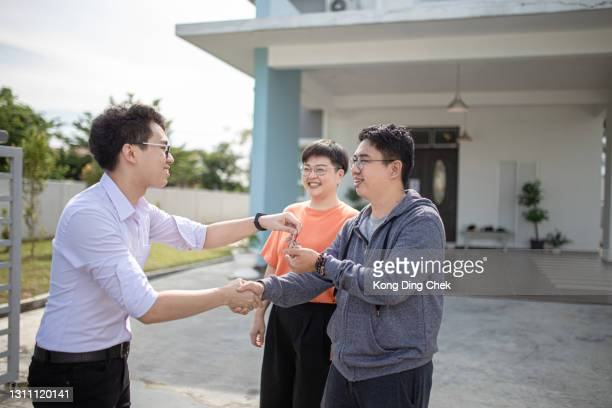 asian chinese family moving into new house and received the house key from real estate agent - mortgage stock pictures, royalty-free photos & images