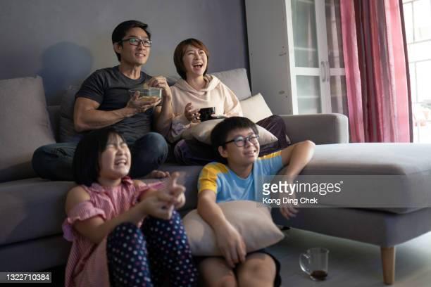 asiatisk kinesisk familj sitter i soffan och tittar på tv hemma tillsammans. - film and television screening bildbanksfoton och bilder