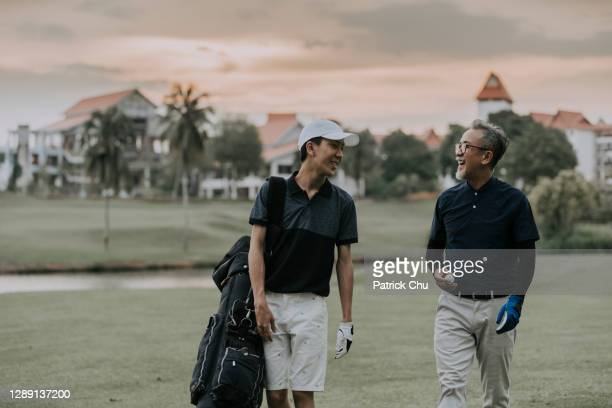 asian chinese father and son golfers walking and having good conversation and smiling at golf course during sunset - country club stock pictures, royalty-free photos & images