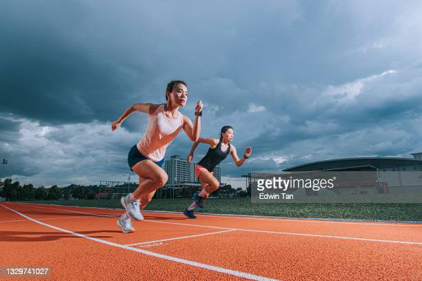 asian chinese female athletes running at track cloudy late evening in track and field stadium - forward athlete stock pictures, royalty-free photos & images