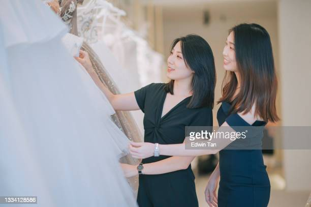 asian chinese female bride and bridesmaid looking for perfect wedding gown wedding dress for her wedding day at bridal shop - wedding dress stock pictures, royalty-free photos & images