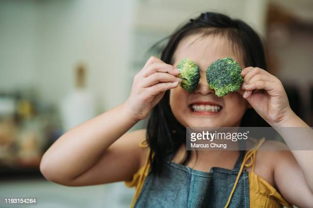 asian chinese female child act cute with hand holding broccoli putting in front of her eyes with smiling face at kitchen - healthy eating stock pictures, royalty-free photos & images