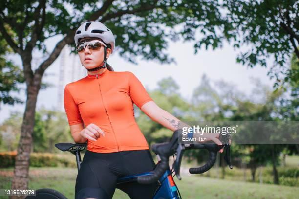 aziatische chinese vrouwelijke fietser die zich bij openbaar park met haar racefiets het fietsen klaarmaakt - wielrennen stockfoto's en -beelden