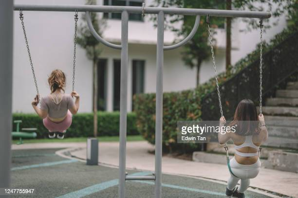 2 asian chinese female friend playing in public park in the morning swing in playground - ventenne foto e immagini stock