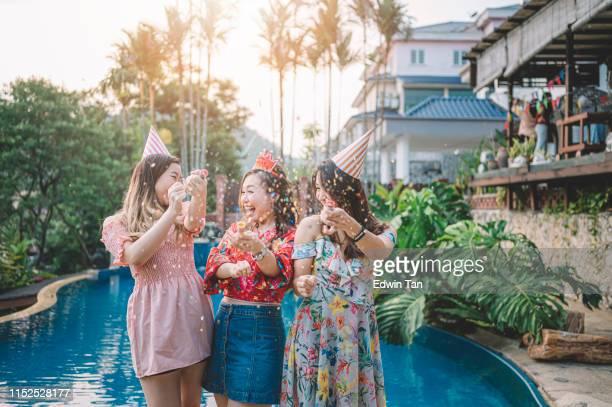 3 asiatique femelle chinoise jouant avec des confettis au bord de la piscine de l'arrière-cour de la maison pendant l'événement de célébration d'anniversaire dans la soirée - celebratory event photos et images de collection