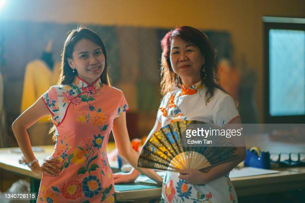 asian chinese female tailor small business owner and her mother standing at work place with chinese tradition clothing cheongsam holding folding fan hands on chin smiling with confidence and satisfaction looking at camera - ambient light stock pictures, royalty-free photos & images