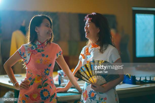 asian chinese female tailor small business owner and her mother standing at work place with chinese tradition clothing cheongsam holding folding fan hands on chin smiling with confidence and satisfaction talking - ambient light stock pictures, royalty-free photos & images