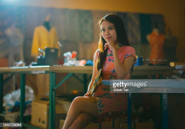 asian chinese female tailor small business owner sitting at her work place with chinese tradition clothing cheongsam holding folding fan hands on chin smiling with confidence and satisfaction - ambient light stock pictures, royalty-free photos & images
