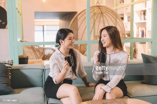 2 asian chinese female white collate worker sitting at lounge sofa relaxing with coffee drink chatting during coffee break session - coffee drink stock pictures, royalty-free photos & images