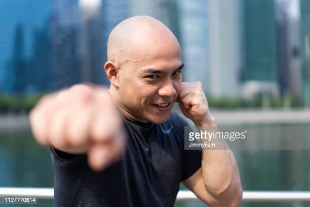 aziatische chinese fitness instructeur, vuist van vertrouwen - vechtkunst stockfoto's en -beelden